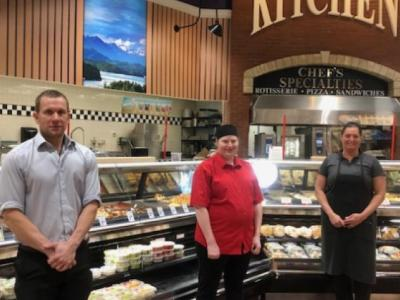 photo of grocery store staff standing with social distancing